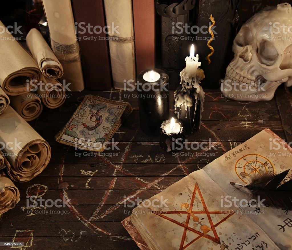Magic book with pentagram, the tarot cards and candles stock photo