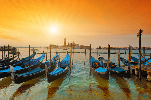 Magic cityscape with gondolas  on the San Marco canal on the background of  Church of San Giorgio Maggiore at sunset in Venice, Italia, Europe.