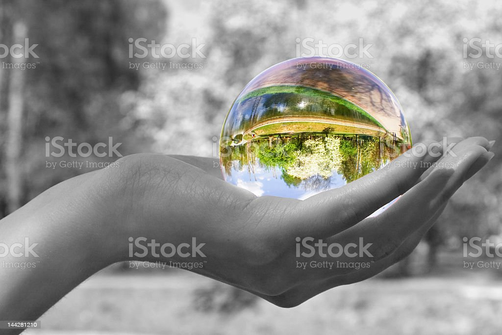 Magic colorful sphere held against black & white background stock photo