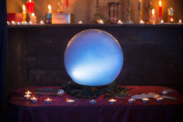 Magic crystal ball with burning candles on  table stock photo