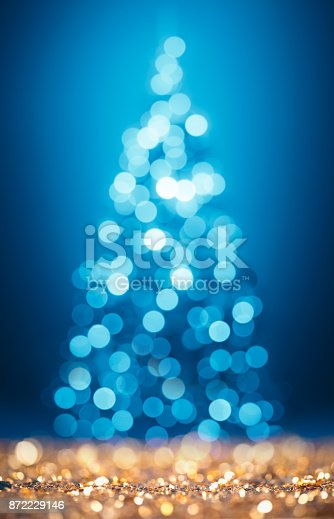 872398892 istock photo Magic defocused Christmas tree on gold glittering surface 872229146