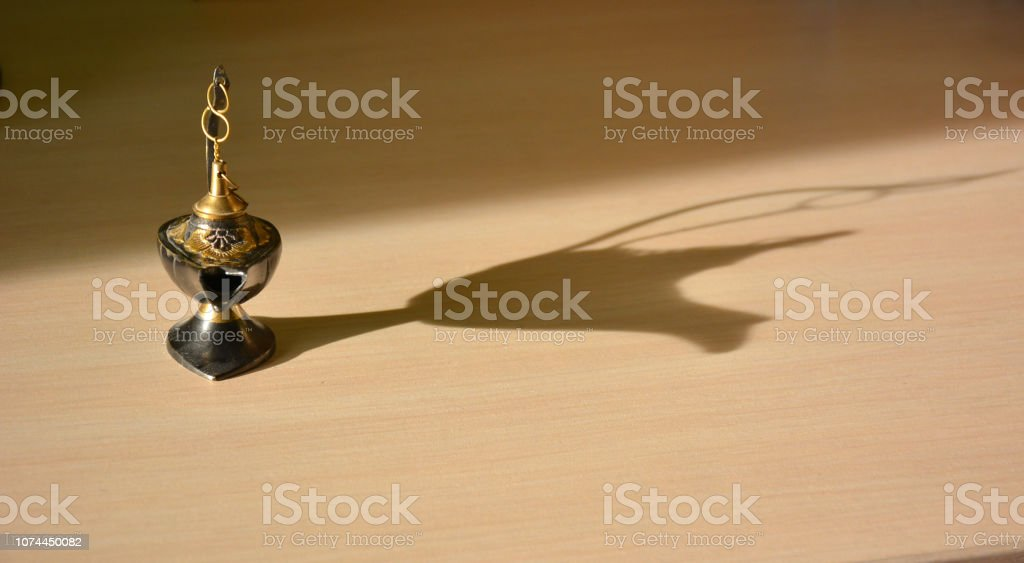 Magic genie lamp with shadows on a light background стоковое фото