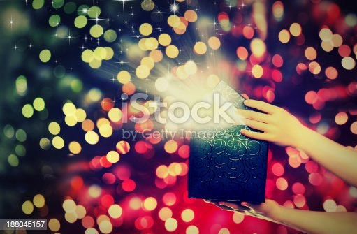 istock magic gift box with lights in their hands 188045157