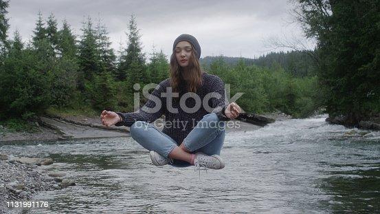 Meditation in mountains. Woman levitating in lotus pose