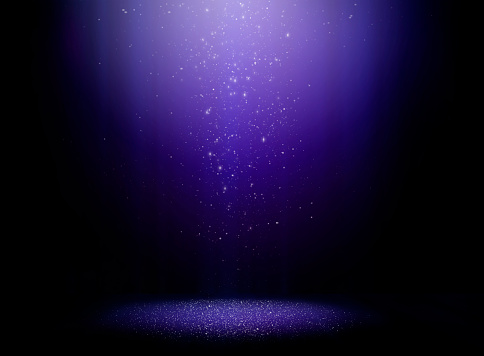 Stage with one light beam and sparkly dust falling from above
