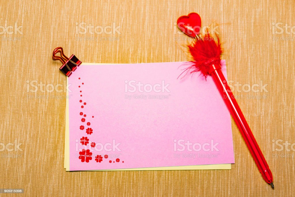 magic pen and paper note with red flowers and paperclip on yellow background, minimal concept and similarities differences stock photo