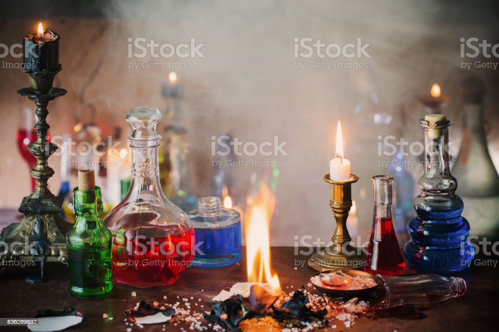 Magic potion, ancient books and candles on dark background stock photo