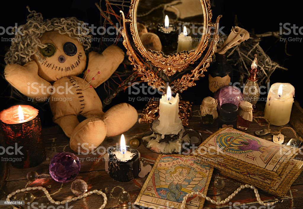 Magic ritual with voodoo doll, mirror and tarot cards stock photo