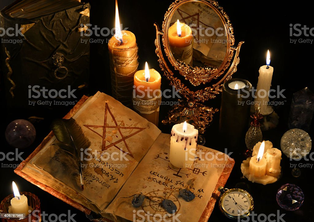 Magic still life with books, burning candles and mirrow stock photo