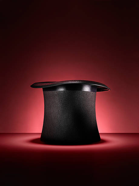 magic top hat on red - Stock Image Shot of a traditional magicians style top hat set up for a trick or illusion on a red background with space left for the designer to add an object or type. magician stock pictures, royalty-free photos & images