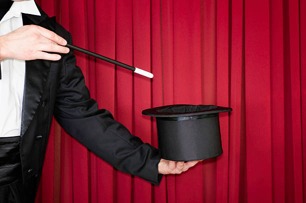 Magic trick on stage Magician on stage doing a trick with top hat magic trick stock pictures, royalty-free photos & images