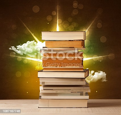 istock Magical books with ray of magical lights and colorful clouds 1087167748