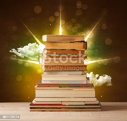 istock Magical books with ray of magical lights and colorful clouds 961179174