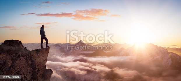 istock Magical Fantasy Adventure Composite of Man Hiking on top of a rocky mountain 1225283682