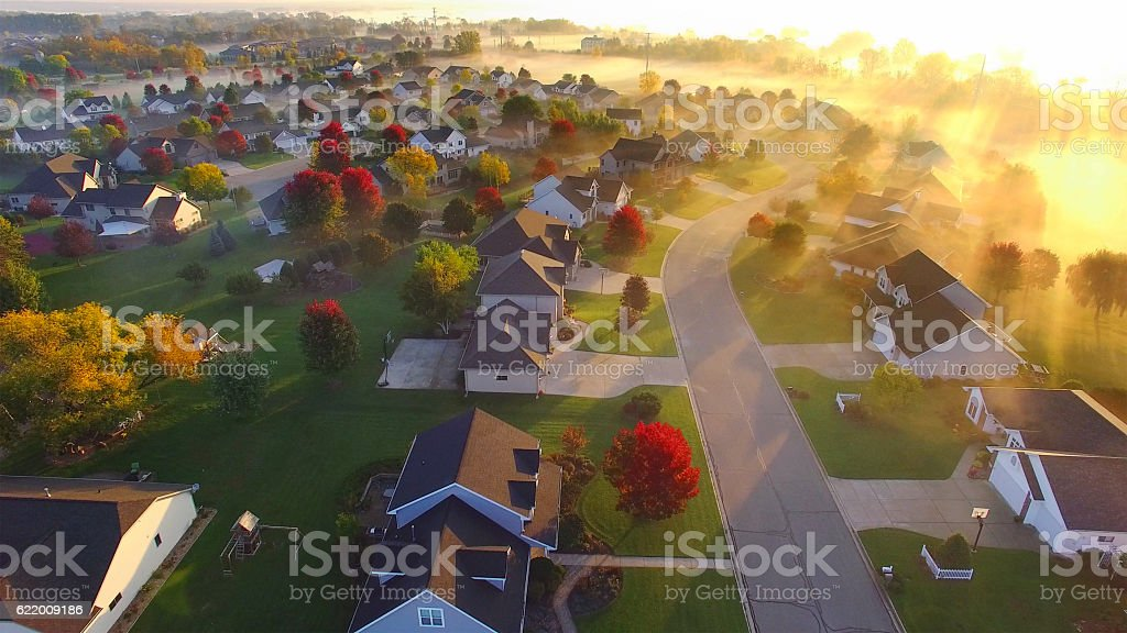 Magical foggy sunrise over sleepy neighborhood with shadows and sunbeams stock photo