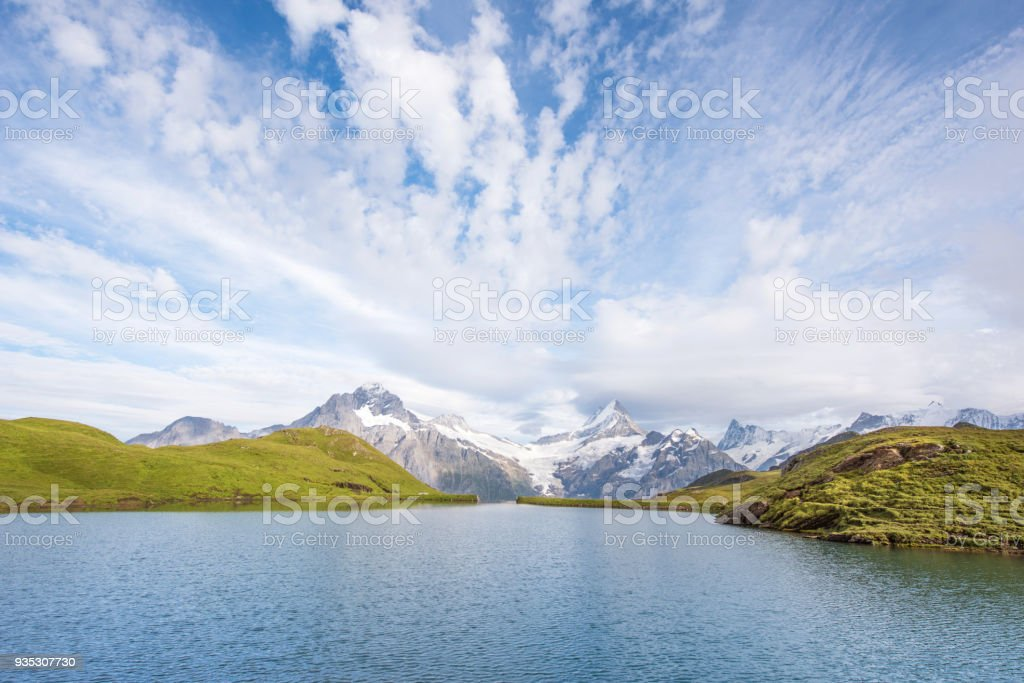 A magical landscape with a lake and clouds  in the mountains in the Swiss Alps, Europe. Wetterhorn, Schreckhorn, Finsteraarhorn et Bachsee. ( relaxation, harmony, anti-stress - concept). stock photo