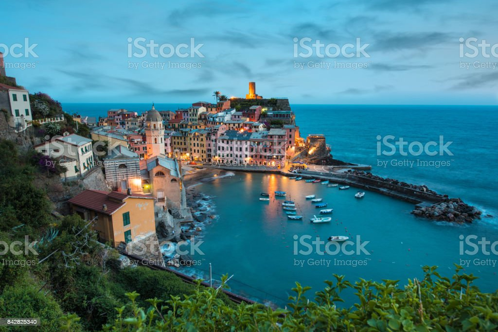 Magical landscape with boats in the bay and colored houses on the rock in Vernazza, Cinque Terre, Italy, Europe at night stock photo
