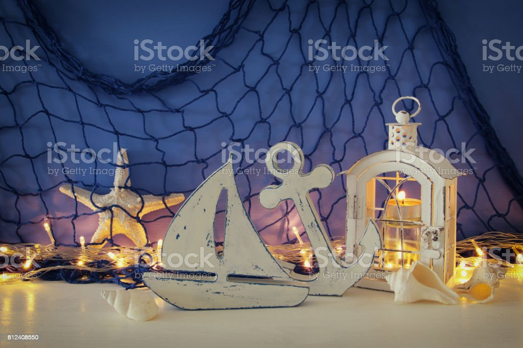Magical lantern with candle light and wooden boat on the shelf. Nautical concept stock photo