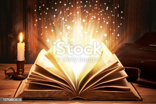 528389419istockphoto Magical old book with sparkles 1070683626