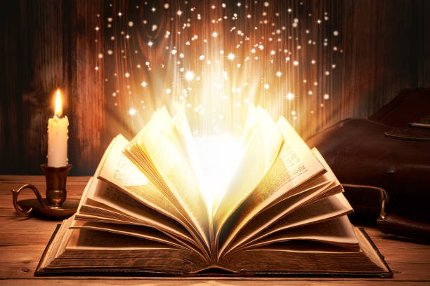 Magical old book with sparkles Old book with magic lights on wooden table by candlelight dreamlike stock pictures, royalty-free photos & images