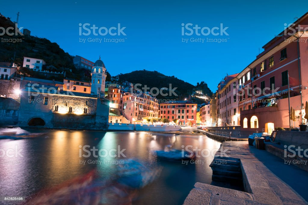 Magical panorama landscape with boats in the bay and colored houses on the rock in Vernazza, Cinque Terre, Italy, Europe at night stock photo