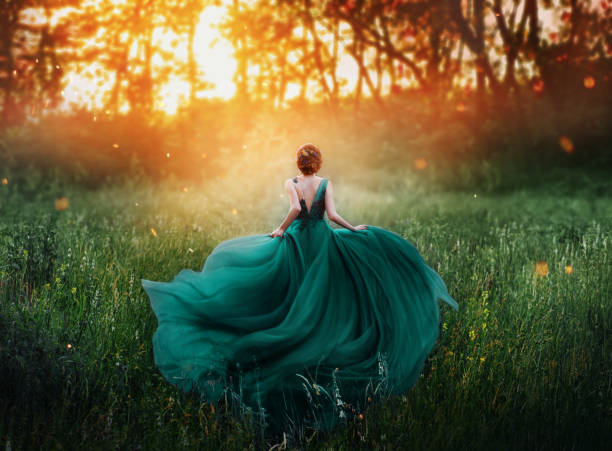 magical picture, girl with red hair runs into dark mysterious forest, lady in long elegant royal expensive emerald green turquoise dress with flying train, amazing transformation during fiery sunset - wedding fashion stock pictures, royalty-free photos & images