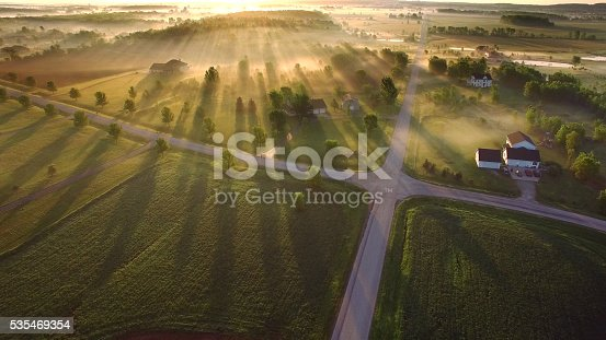 Magical sunrise through ground fog with long shadows and sunbeams.