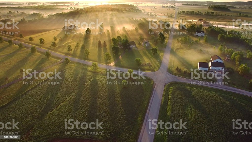 Magical sunrise through ground fog with long shadows and sunbeams stok fotoğrafı