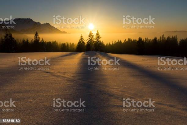 Photo of Magical sunset in a snowy mountain landscape. Sunbeams and backlighting.
