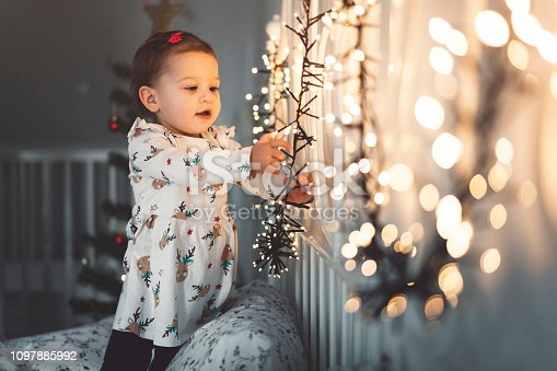 Little baby girl, one year old girl, on the bed, in the bedroom, looking at christmas lights. White floral bedding. Baby wearing festive christmas dress with reindeers on it.