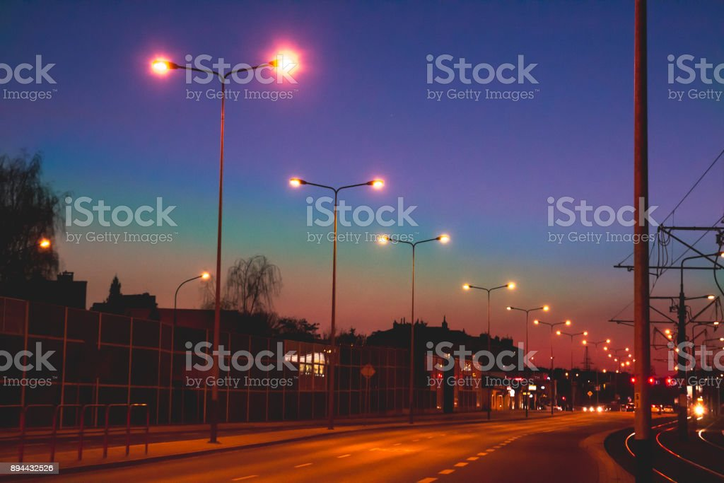 Magically beautiful evening empty road with glowing lights in the dusk at sunset, blurry, toned stock photo