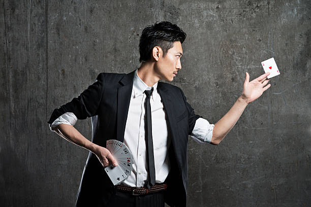 Magician doing card tricks An Asian magician performing card tricks against a grungy background  magic trick stock pictures, royalty-free photos & images