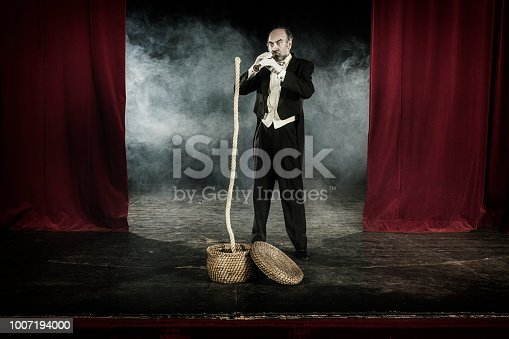 Magician doing snake charmer trick with rope