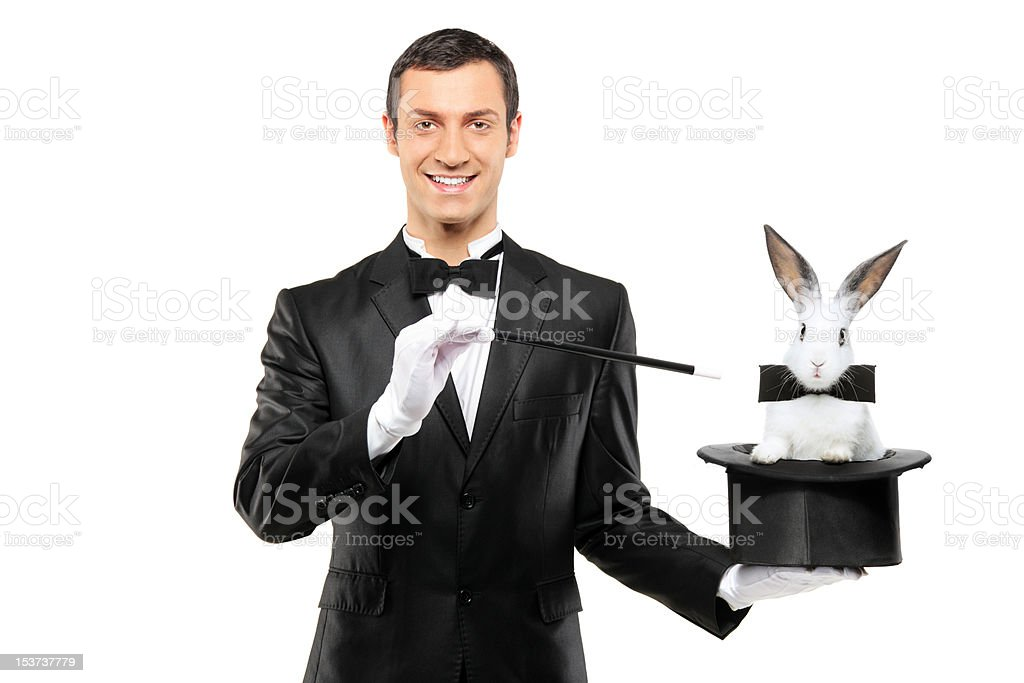 Magician holding a top hat with rabbit in it stock photo
