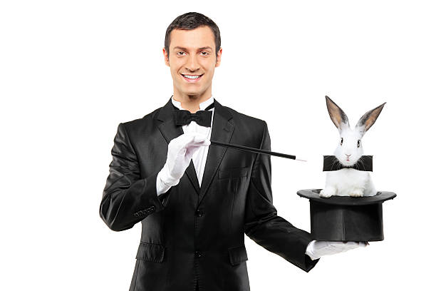 Magician holding a top hat with rabbit in it A magician in a black suit holding a top hat with a rabbit in it isolated on white background magician stock pictures, royalty-free photos & images