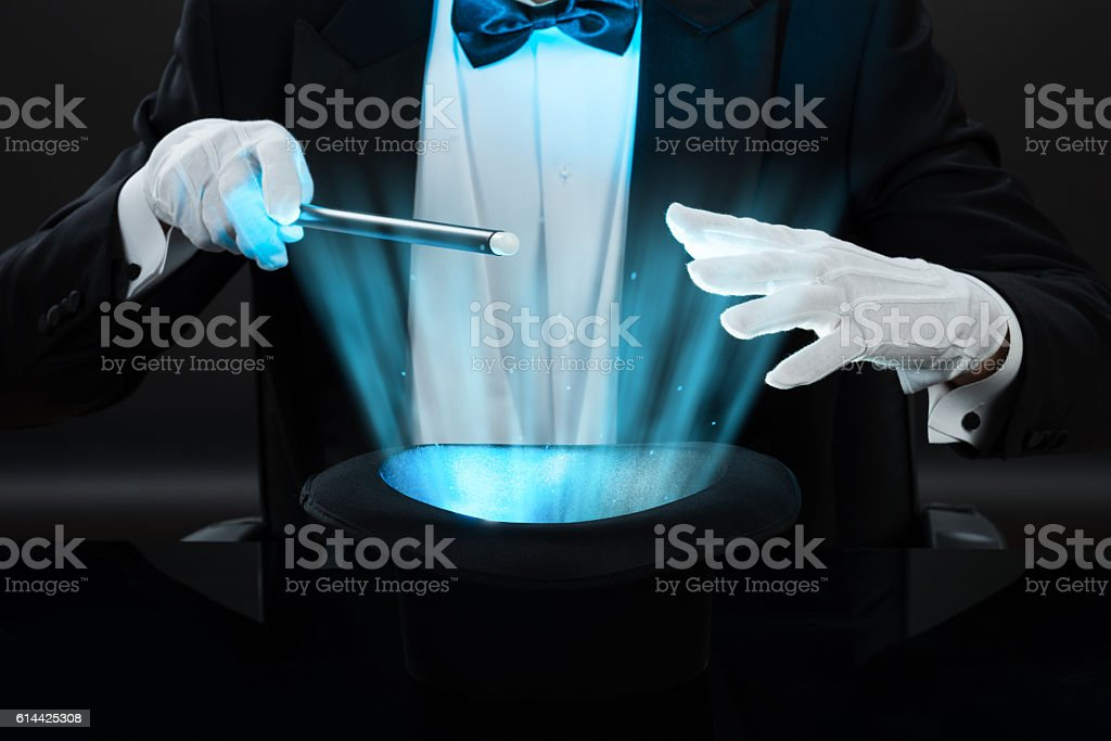 Magician Holding Magic Wand Over Illuminated Hat stock photo