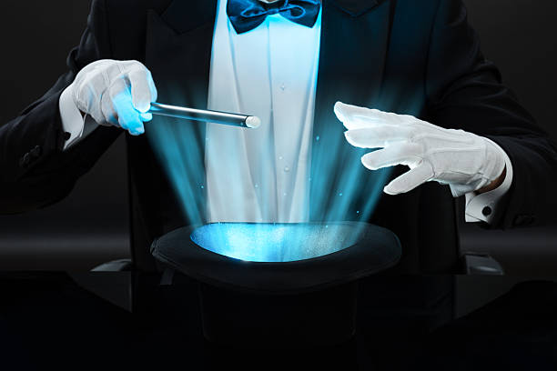 magician holding magic wand over illuminated hat - magician stock photos and pictures