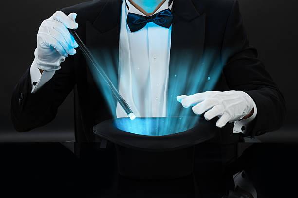 Magician Holding Magic Wand Over Illuminated Hat stock photo