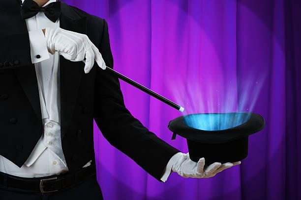 Magician Holding Wand Over Illuminated Hat stock photo