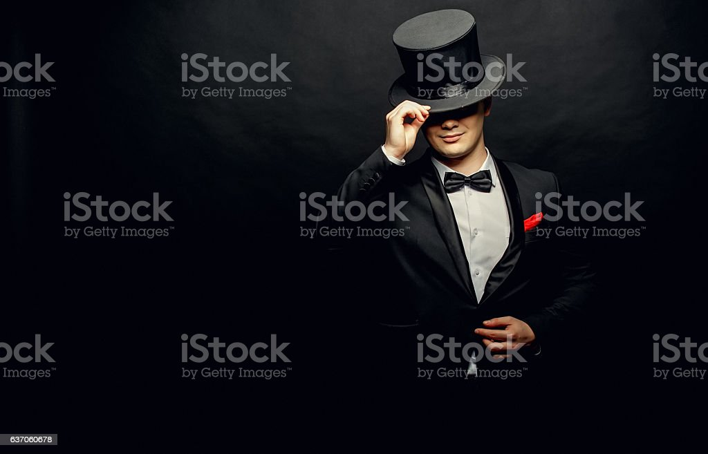magician in a black suit holding stock photo