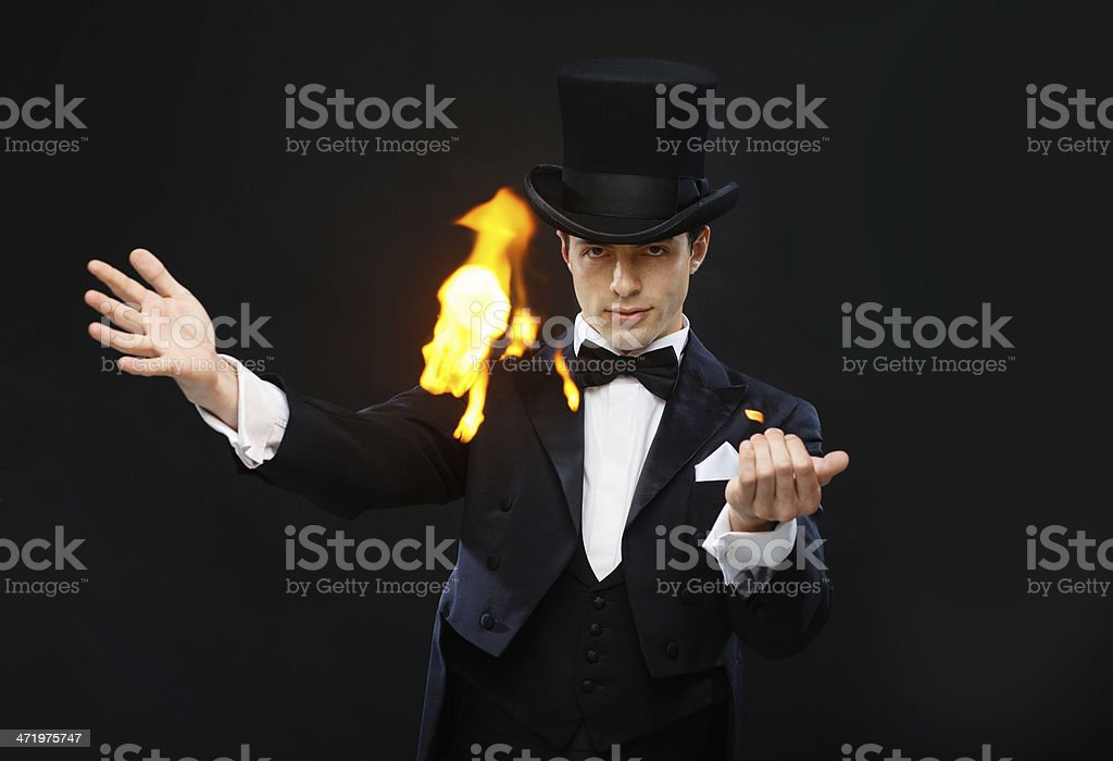 magician in top hat showing trick with fire stock photo