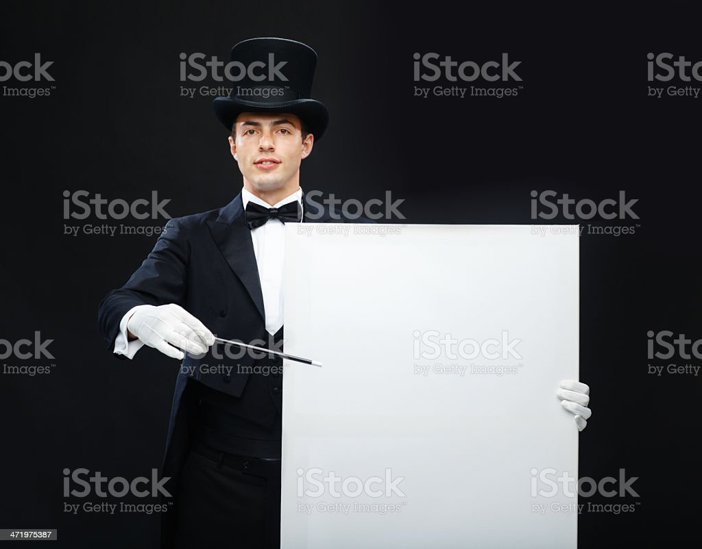magician in top hat with magic wand showing trick stock photo