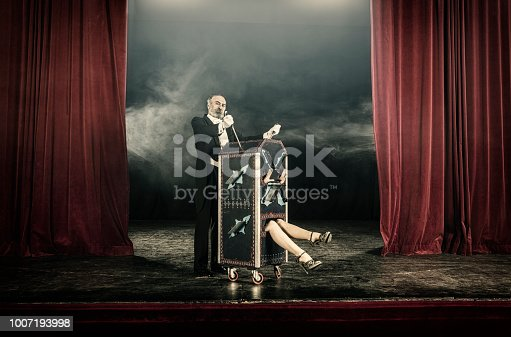 Magician inserting swords in box occupied by female assistant
