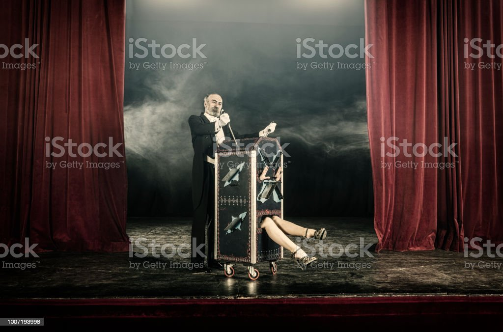 Magician inserting swords in box occupied by female assistant stock photo
