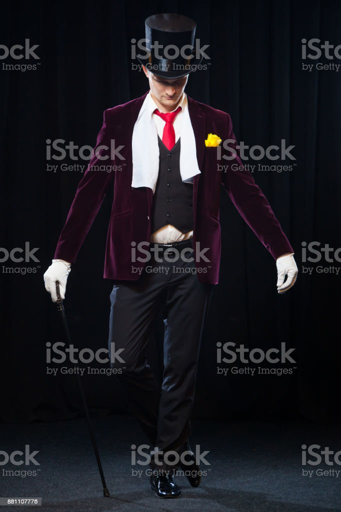 Magician, Juggler man, Funny person, Black magic, Illusion standing on the stage with a cane of beautiful light stock photo