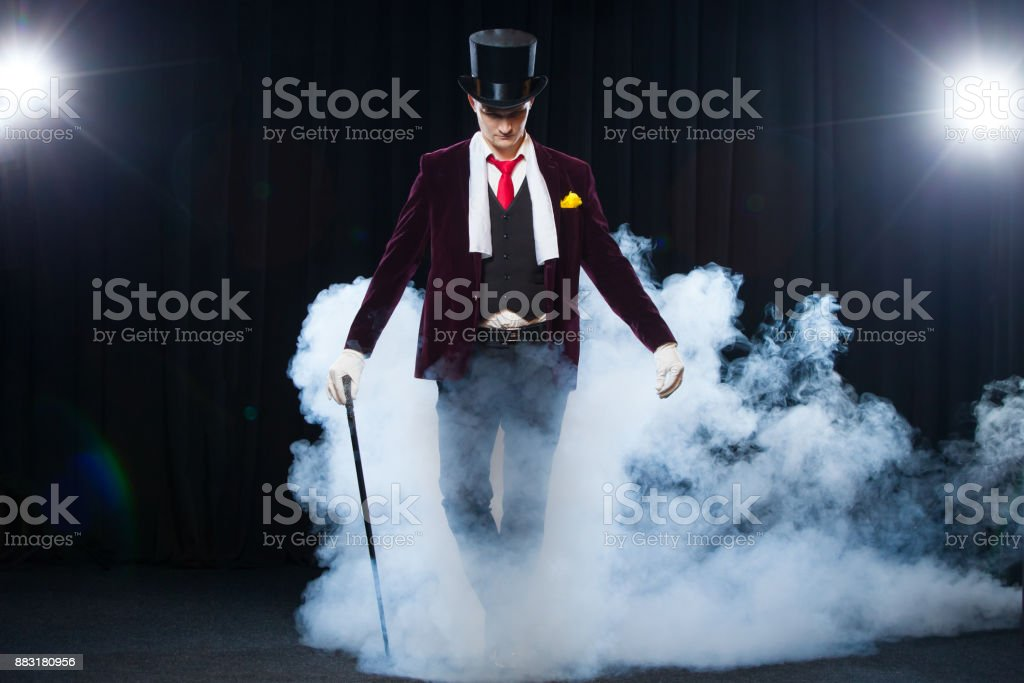 Magician, Juggler man, Funny person, Black magic, Illusion standing on the stage with a cane of beautiful light. shrouded in a beautiful mysterious smoke stock photo