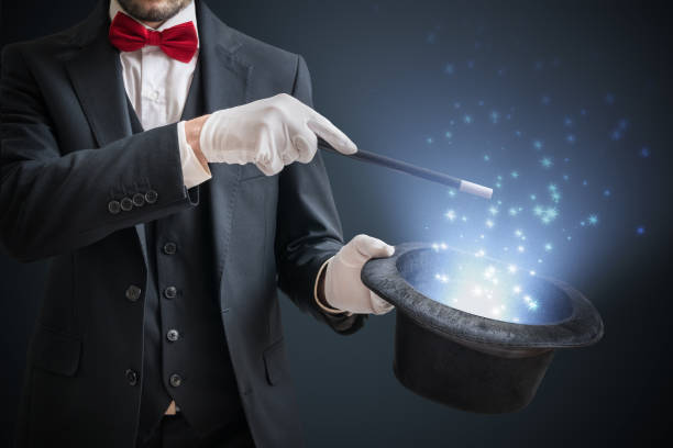 magician or illusionist is showing magic trick. blue stage light in background. - magician stock photos and pictures