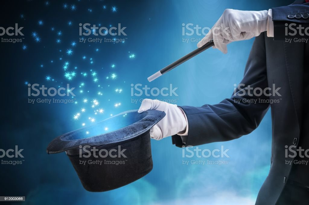 Magician or illusionist is showing magic trick. Blue stage light in background. stock photo
