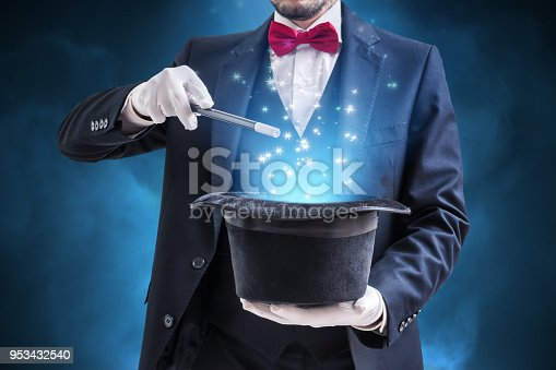 Magician or illusionist is showing magic trick. Blue stage light in background.