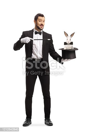 Full length portrait of a magician performing a trick with a hat and a rabbit isolated on white background